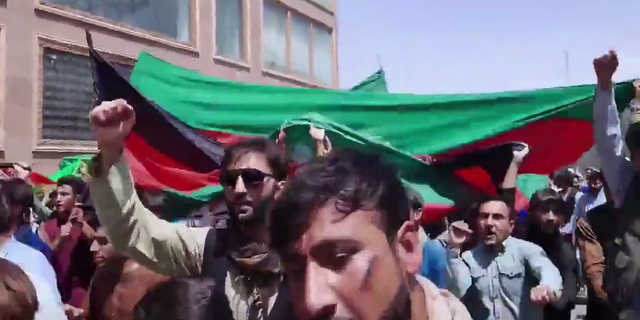Demonstrators are seen marching in Kabul on Thursday, waving the Afghanistan flag.