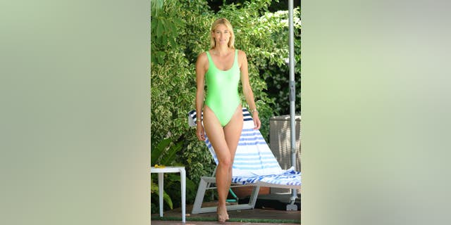 Kristen Taekman is seen wearing a neon swimsuit while relaxing by the pool in Long Island, N.Y.