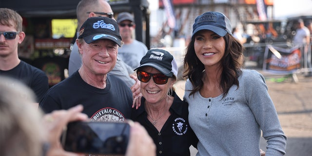 STURGIS, SOUTH DAKOTA - AUGUST 09: Governor Kristi Noem of South Dakota (R) poses for pictures at the Sturgis Buffalo Chip campground after riding in the Legends Ride for charity on August 09, 2021 near Sturgis, South Dakota. (Photo by Scott Olson/Getty Images)