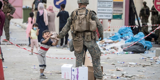 En este agosto. 20, 2021, photo provided by the U.S. Marine Corps, a Marine with the 24th Marine Expeditionary Unit (MEU) provides a meal ready-to-eat to a child during an evacuation at Hamid Karzai International Airport in Kabul, Afganistán.
