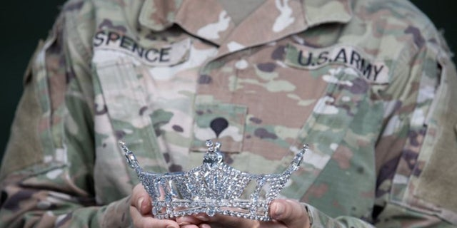 Army Spc. Maura Spence holds her crown.