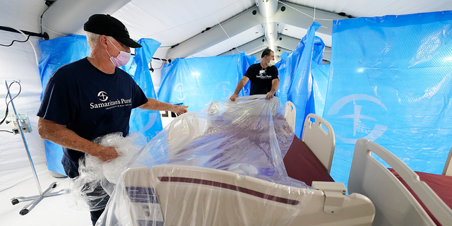 Samaritan's Purse staff set up a portable bed at a field hospital and monoclonal antibody clinic opened by the U.S. Department of Health and Human Services at the University of Mississippi Medical Center in response to the rising number of COVID-19 cases in the state. (AP Photo/Rogelio V. Solis)