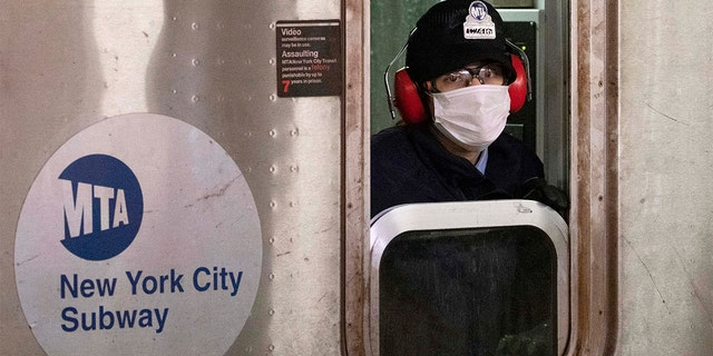 FILE — In this April 18, 2020 file photo, a subway conductor wears a face mask as the train is in a station, in the Bronx borough of New York. New York Gov. Andrew Cuomo and New York City Mayor Bill de Blasio have scheduled competing news conferences Monday, Aug. 2, 2021, amid rising COVID-19 case counts attributed to the highly contagious delta variant of the virus. (AP Photo/Mark Lennihan, File)