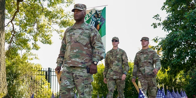"""Member of the U.S. military head toward the practice field for the """"Back Together Saturday"""" during NFL football training camp for the Philadelphia Eagles, Saturday, July 31, 2021, in Philadelphia. (AP Photo/Chris Szagola)"""