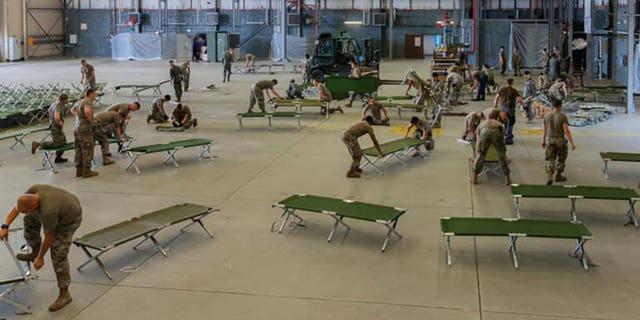 US-Militärangehörige und Freiwillige bereiten Feldbetten vor, um den Flughafen Rammstein in Deutschland zu verlassen.  (Flughafen Rammstein)
