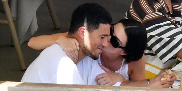 Out in the glorious sunshine during their Italian holiday in Salerno, the American model and reality star Kendall Jenner packed on the PDA by holding hands with her NBA star and boyfriend Devin Booker. Making their way to a restaurant the couple sat down to enjoy a little fine Italian dining with Jenner wearing her floral-patterned vest top and a green mini skirt, as the pair continued their affectionate ways with a touchy-feely display and a kiss at the dining table. After enjoying their dining experience, Jenner and Booker headed back to their superyacht and soaked up the blazing hot sunshine, as Jenner showed off her sexy physique in her skimpy little bikini during her romantic Italian getaway.
