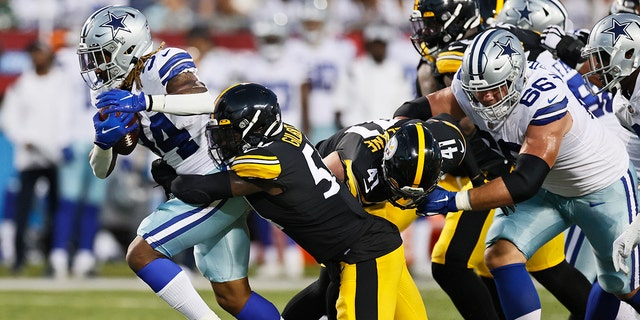 Dallas Cowboys running back Rico Dowdle (34) tries to escape the grasp of Pittsburgh Steelers linebacker Ulysees Gilbert III during the first half of the Pro Football Hall of Fame NFL preseason game Thursday, Aug. 5, 2021, in Canton, Ohio. (Associated Press)