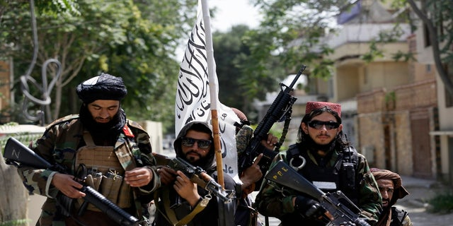 Taliban fighters display their flag on patrol in Kabul, Afghanistan, on Thursday.