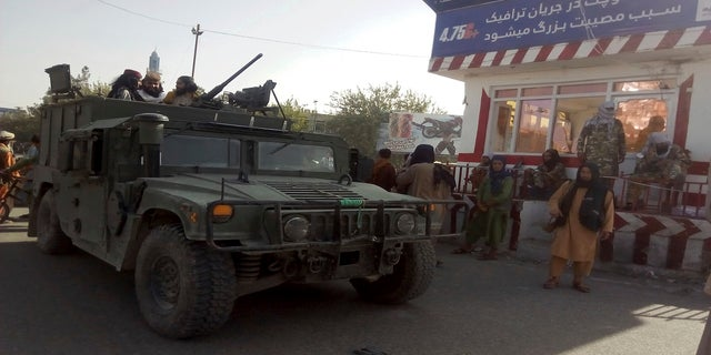 Taliban fighters stand guard at a checkpoint in Kunduz city, northern Afghanistan, on Monday. (AP)