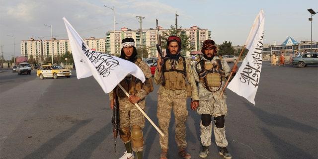 Taliban fighters hold Taliban flags in Kabul, Afganistán, lunes, ago. 30, 2021. (AP Photo/Khwaja Tawfiq Sediqi)