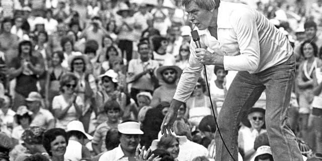 Tom T-Hall si sporge sul bordo del palco in un accampamento del 1977 sulle colline per incontrare persone vicino a St. Clairsville, Ohio.  (Agenzia di stampa)
