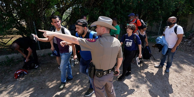 In this Wednesday, June 16, 2021, file photo, a Texas Department of Public Safety officer in Del Rio, Texas, directs a group of migrants who crossed the border and turned themselves in. (AP Photo/Eric Gay, File)