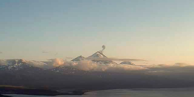 In this webcam image provided by the Alaska Volcano Observatory, is the Pavlof Volcano in a state of eruption with episodic low-level ash emissions on Thursday, Aug. 5, 2021. Three remote Alaska volcanos are each in a state of eruption, one producing lava and the other two blowing steam and ash. So far, no small communities near any of the three have been impacted, Chris Waythomas, a geologist with the Alaska Volcano Observatory, said Thursday. (Alaska Volcano Observatory via AP)