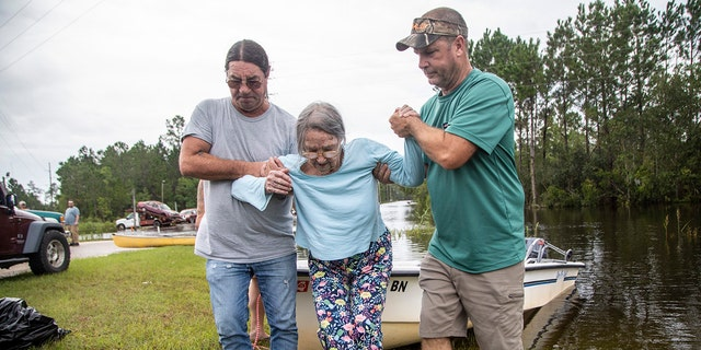 Stanley Delle, left, and Jeff Delle help 80-year-old Eileen Delle onto dry land Monday, Aug. 30, 2021 after floodwaters from Hurricane Ida surrounded her elevated home in the Shoreline Park community in Bay St. Louis.
