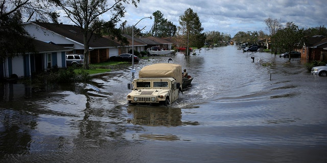 A National Guard vehicle drives through floodwater left behind by Hurricane Ida in LaPlace, Louisiana, on Monday, Aug. 30, 2021. The storm, wielding some of the most powerful winds ever to hit the state, drove a wall of water inland when it thundered ashore Sunday as a Category 4 hurricane and reversed the course of part of the Mississippi River.