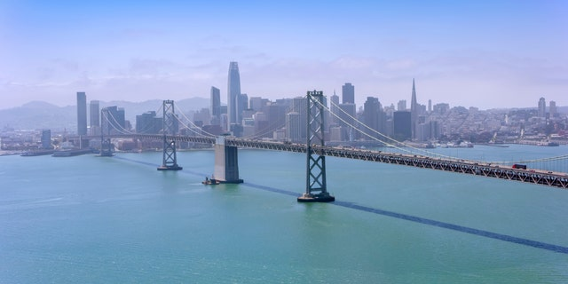 Aerial view of the San Francisco-Oakland Bay Bridge with modern cityscape in background, サンフランシスコ, カリフォルニア, 米国.