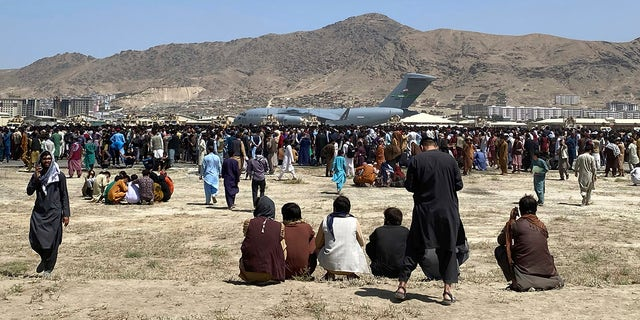 Hundreds of people gather near a U.S. Air Force C-17 transport plane at a perimeter at the international airport in Kabul, Afganistán, el lunes.