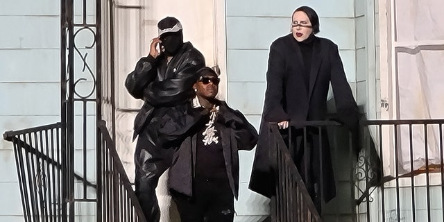 From left, a masked Kanye West, DaBaby, and Marilyn Manson hang out on the steps of a replica of the home of West's late mother, Donda, at Soldier Field in Chicago, Aug. 26, 2021. (Brian Prahl/MEGA)
