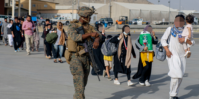 U.S. Marines assigned to 24th Marine Expeditionary Unit escorts evacuees during an evacuation at Hamid Karzai International Airport, Afghanistan, Aug. 18. (U.S. Marine Corps photo by Lance Cpl. Nicholas Guevara)