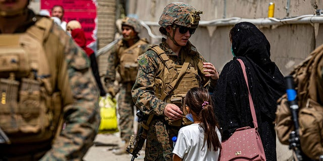 A @USMC Marine assists a woman and child during an evacuation at Hamid Karzai International Airport in Kabul, Afghanistan. #HKIA