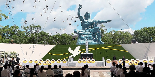 Doves fly over the Statue of Peace during a ceremony at Nagasaki Peace Park in Nagasaki, southern Japan Monday, 八月. 9, 2021. The Japanese city of Nagasaki on Monday marked its 76th anniversary of the U.S. atomic bombing. (Kyodo News via AP)
