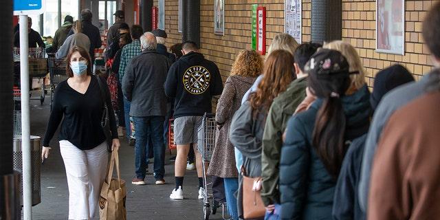 2021年8月17日、ニュージーランドオークランドのスーパーマーケットに入るために買い物客が並んでいます。 ニュージーランドの政府は火曜日たった一人のコロナウイルスのコミュニティの事例を検出した後、全国を厳格閉鎖措置に移行する抜本的な対策をとりました。  (ブレットピップ/ニュージーランドヘラルド(AP))
