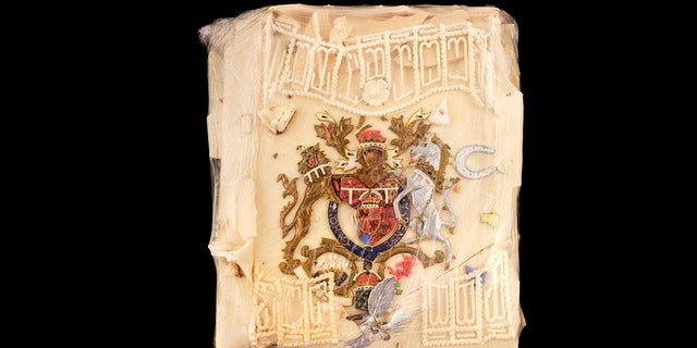 The wedding cake slice has a coat-of-arms design colored in red, silver, gold and blue. It also features a small silver horseshoe and leaf spray with white decorative icing.(Dominic Winter Auctioneers via AP)