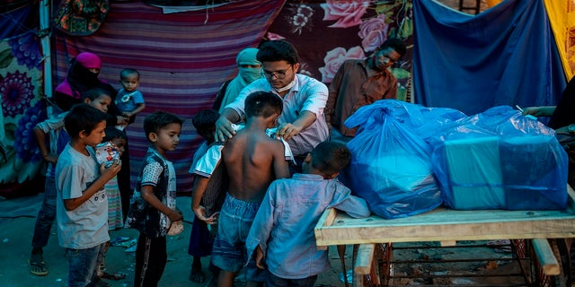 A Rohingya activist distributes new clothes among refugees at a refugee camp alongside the banks of the Yamuna River in the southeastern borders of New Delhi, sprawling Indian capital, on July 1.