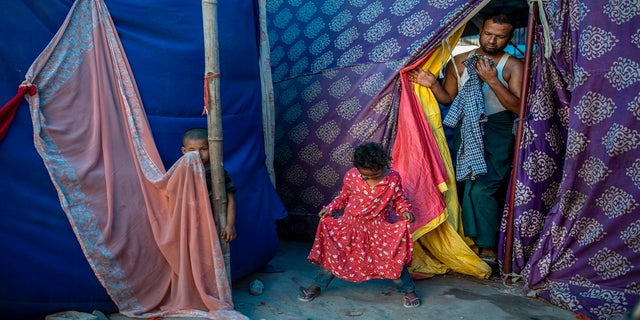 Kids play as Salimullah, 35, a Rohingya refugee comes out of his tent at a refugee camp alongside the banks of the Yamuna River in the southeastern borders of New Delhi on July 1. (AP)