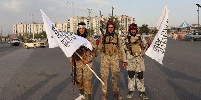 Taliban fighters hold Taliban flags in Kabul, Afghanistan, Monday, Aug. 30, 2021. (AP Photo/Khwaja Tawfiq Sediqi)