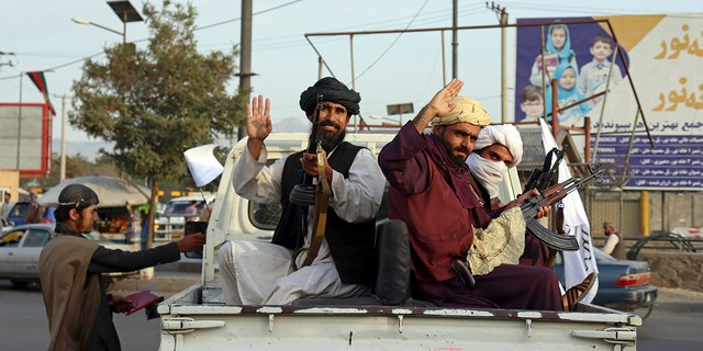 Taliban fighters wave from the back of a van in Kabul, Afghanistan, Monday, August 30, 2021. Many Afghans are worried about the Taliban regime and are looking for ways out of Afghanistan.  But it is financial desperation that seems to weigh heavily on the city.