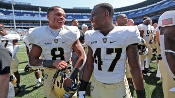 Army football players run out on field carrying American flags