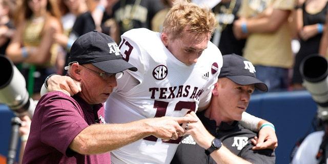 텍사스 A&앰프;M quarterback Haynes King, 센터, is helped off the field after being injured in the first half of an NCAA college football game against Colorado, 토요일, 씨족. 11, 2021, 덴버.