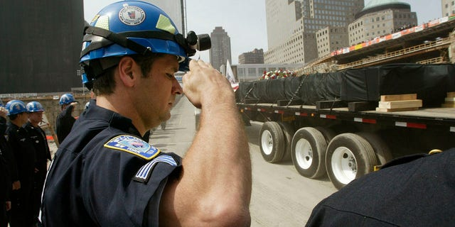 FILE – The final beam to be cut down at the World Trade Center is driven away on a truck shrouded in black as New York and New Jersey Port Authority Police salute during a ceremony to mark the end of the recovery effort on the site in New York, Mei 30, 2002. The beam was the ceremonial last load to be taken from the site. The World Trade Centers collapsed when attacked by hijacked airplanes September 11, 2001. REUTERS/Mike Segar MS