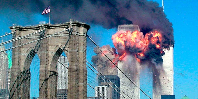 FILE – The second tower of the World Trade Center bursts into flames after being hit by a hijacked airplane in New York in this September 11, 2001 file photograph. The Brooklyn bridge is seen in the foreground.  REUTERS/Sara K. Schwittek