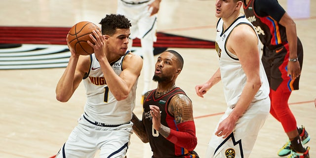 Portland Trail Blazers guard Damian Lillard (0) defends Denver Nuggets forward Michael Porter Jr.. (1) in the first half during game six in the first round of the 2021 NBA Playoffs. at Moda Center.