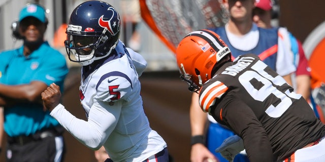 Houston Texans quarterback Tyrod Taylor (5) rushes for a 15-yard touchdown against Cleveland Browns defensive end Myles Garrett (95) during the first half of an NFL football game, Sunday, Sept. 19, 2021, in Cleveland.