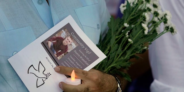 An attendee at a community vigil honoring the life of Dustin Wakefield, holds a program, flowers and a battery-powered candle, Tuesday, Aug. 31, 2021, in Miami Beach, Fla. Wakefield, 21, was shot and killed last week by gunman who walked into a Miami Beach restaurant and fatally shot Wakefield who was vacationing from Castle Rock, Colo. (AP Photo/Wilfredo Lee)