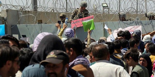 26 अगस्त, 2021 को अफगानिस्तान के काबुल में हामिद करजई अंतरराष्ट्रीय हवाई अड्डे की परिधि पर एक निकासी नियंत्रण चौकी के पास सैकड़ों लोग इकट्ठा होने के कारण एक अमेरिकी सैनिक एक गेट बंद होने का संकेत देता है। (एपी फोटो/वली सबावून, फाइल )