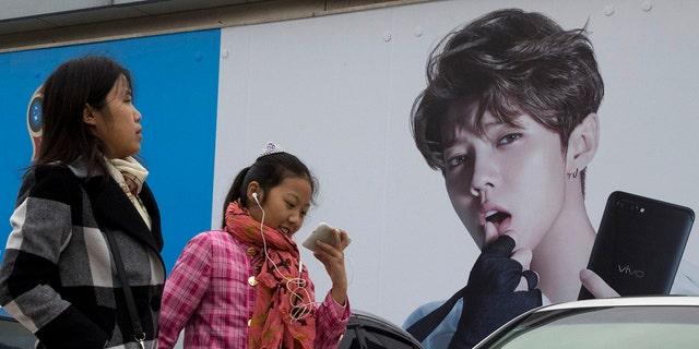 Nesta foto de arquivo de 2017, as mulheres chinesas pularam um anúncio do ídolo adolescente Lu Han, também conhecido como Justin Bieber da China, em Pequim.