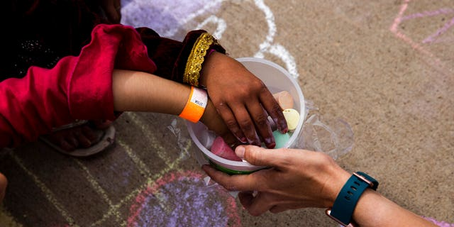 """In this Aug. 31 , 2021, photo provided by the U.S. Army, Afghan children take a piece of chalk at a children's activity event held by non-governmental charities at Fort McCoy in Wisconsin. U.S. officials are looking into reports that in the frantic evacuation of desperate Afghans from Kabul, older men were admitted together with young girls they claimed as """"brides"""" or otherwise sexually abused. One internal document seen by The Associated Press says the State Department has sought """"urgent guidance"""" from other agencies after purported child brides were brought to Fort McCoy. (Spc. Rhianna Ballenger/U.S. Army via AP)"""