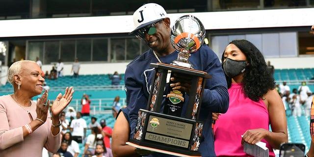 Huấn luyện viên trưởng của Jackson State, Deion Sanders, cầm chiếc cúp Orange Blossom Classic sau khi giành chiến thắng trong trận đấu bóng đá đại học NCAA trước Florida A & amp; M, Chủ nhật, ngày 5 tháng 9 năm 2021, tại Miami Gardens, Florida.