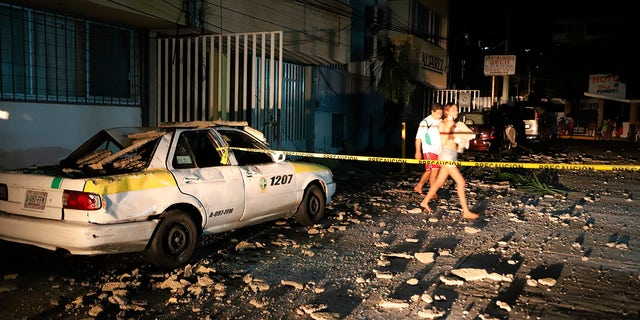 A couple walks past a taxi cab that was damaged by falling debris after a strong earthquake in Acapulco, Mexico, Tuesday, Sept. 7, 2021. (AP Photo/ Bernardino Hernandez)