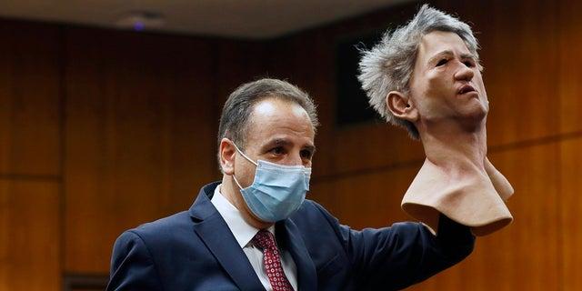 Deputy District Attorney Habib A. Balian holds a rubber latex mask, worn by Robert Durst when police arrested him, 수요일, 씨족. 8, 2021 잉글 우드, 칼리프. (Al Seib/Los Angeles Times via AP, 풀)