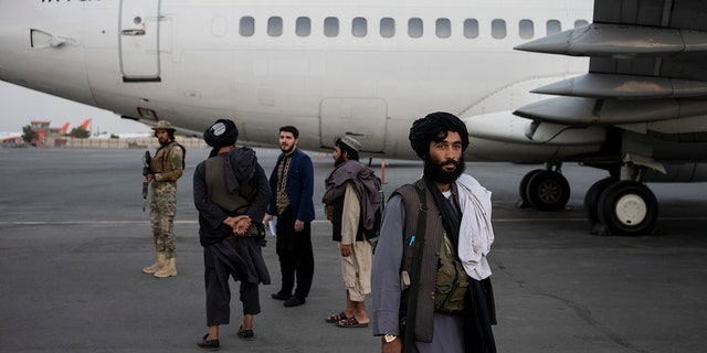 Taliban personnel stand beside a plane at the airport in Kabul, 阿富汗, 星期四, 九月. 9, 2021. (AP Photo/Bernat Armangue)