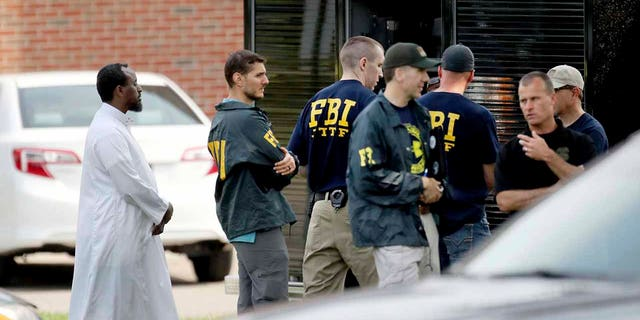 In this Aug. 15, 2017, 파일 사진, law enforcement officials investigate the site of an explosion at the Dar Al-Farooq Islamic Center in Bloomington, 민.