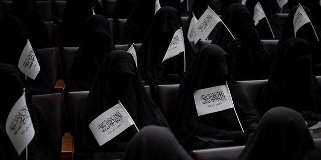 Phụ nữ vẫy cờ Taliban khi họ ngồi bên trong khán phòng tại trung tâm giáo dục của Đại học Kabul trong cuộc biểu tình ủng hộ chính phủ Taliban ở Kabul, Afghanistan, Thứ Bảy, ngày 11 tháng 9 năm 2021.