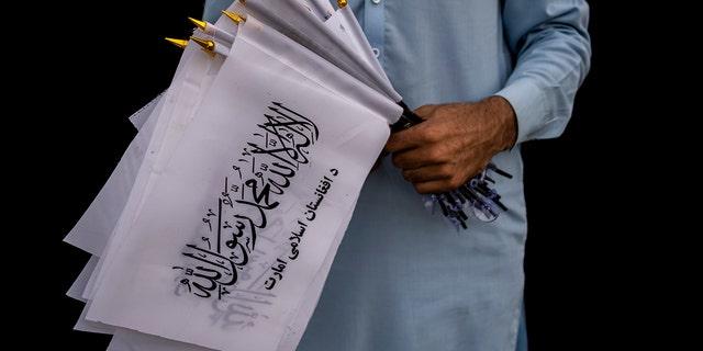 Một người bán hàng rong bán cờ Taliban đợi khách bên ngoài khuôn viên đại sứ quán Mỹ ở Kabul, Afghanistan, thứ Bảy, ngày 11 tháng 9 năm 2021.