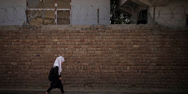 A girl walks to school before class in Kabul, Afghanistan, Sunday, Sept. 12, 2021.