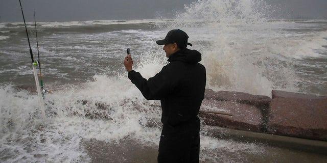 Frank Rivera streams a Facebook live as he fishes with a friend while Tropical Storm Nicholas heads toward the Texas coast, Monday, Sept. 13, 2021, along the seawall in Galveston, Texas. (Jon Shapley/Houston Chronicle via AP)
